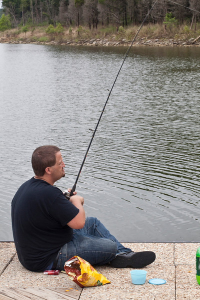 Tim Miller sits on the Possum Ridge Boat dock fishing. His brother Jason admitted that they have eaten fish from the lake this summer without any ill effect.