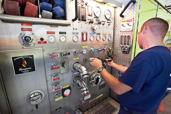 Captain Chris Fries Jr does a routine check on one of the fire truck's instrument panels.
