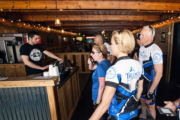 Big Four Burgers + Beer employee Sam Nedvidek greets cyclists from Trilogy Health Services after they completed a fifteen mile journey from Louisville's East End to Jeffersonville.