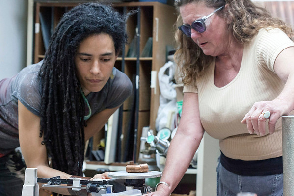Student Rachel Broaddus weighs out some raw materials under the instruction of teacher Laurie Adkins.