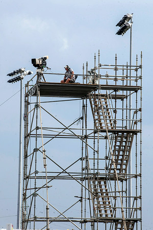 A lone cameraman sits atop a multi-story scaffolding ready for the action.