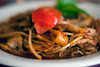 Pad Keemow is pan-fried rice noodles with beef, basil paste, bean sprouts and tomatoes.