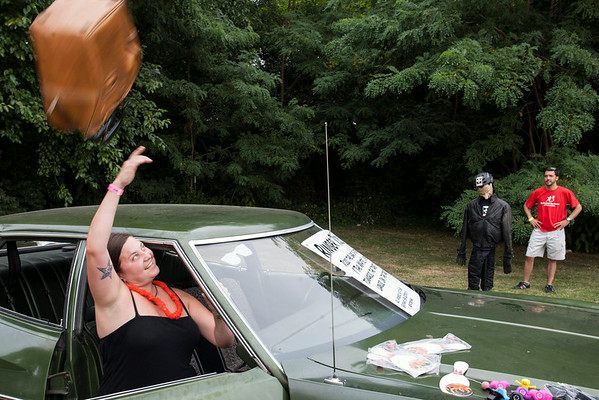 """Lindsay Shaw takes a turn at the """"Ringer Toss"""" during Lebowski Fest on Saturday. The contest challenged participants to strike the Nixon dummy with an old leather bag while remaining seated in the vehicle."""