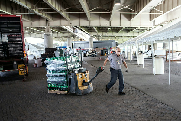 A Coca-Cola driver unloads pallets of product along the food and vendor area under I-64.