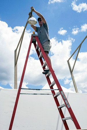 Doug Pohl installs lighting above one of the many exhibits on the great lawn.
