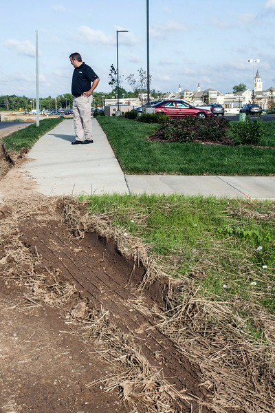 Culver's owner Jason Behnke investigates the damage from delivery trucks entering the Outlet Shoppes of the Bluegrass. His landscaping and irrigation system have been damaged due to a tight turn at the entrance.
