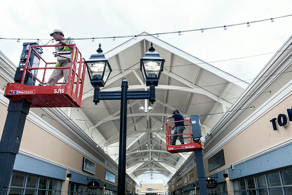 Construction workers and store employees at the Outlet Shoppes of the Bluegrass put on the finishing touches as the official opening of the complex on Thursday looms.
