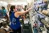 Ashley Hatcher of Claire's Outlet stocks a wall of bracelets and earrings as her employees sort the merchandise on a packed floor.