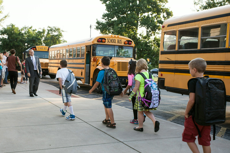 Principal Kyle Lanoue greets incoming students as they arrive by bus at Grant Line Elementary on Thursday morning for the first day of school in Southern Indiana.