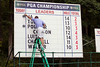 PGA workers update the leaderboard near hole #15 at Valhalla on Thursday afternoon.