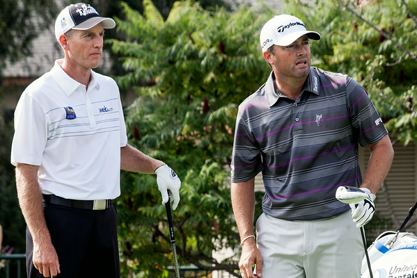 Jim Furyk and Ryan Palmer watch as Palmer's drive sails down the fairway of hole #10.