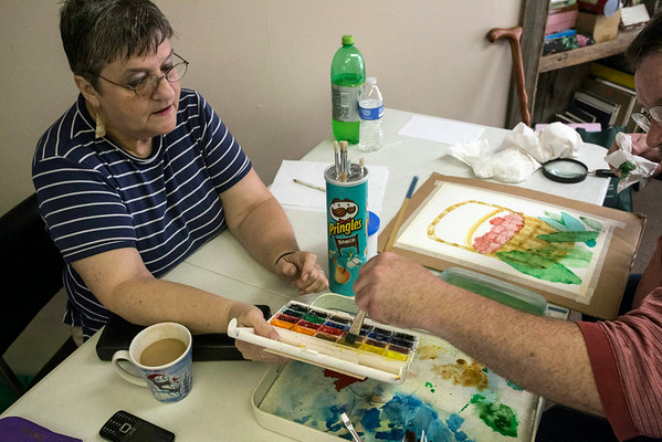 Artist Marlis Nichols assists Kevin Hooks with his color selection. Wounds sustained in combat have left Hooks with limited vision and severe color blindness.