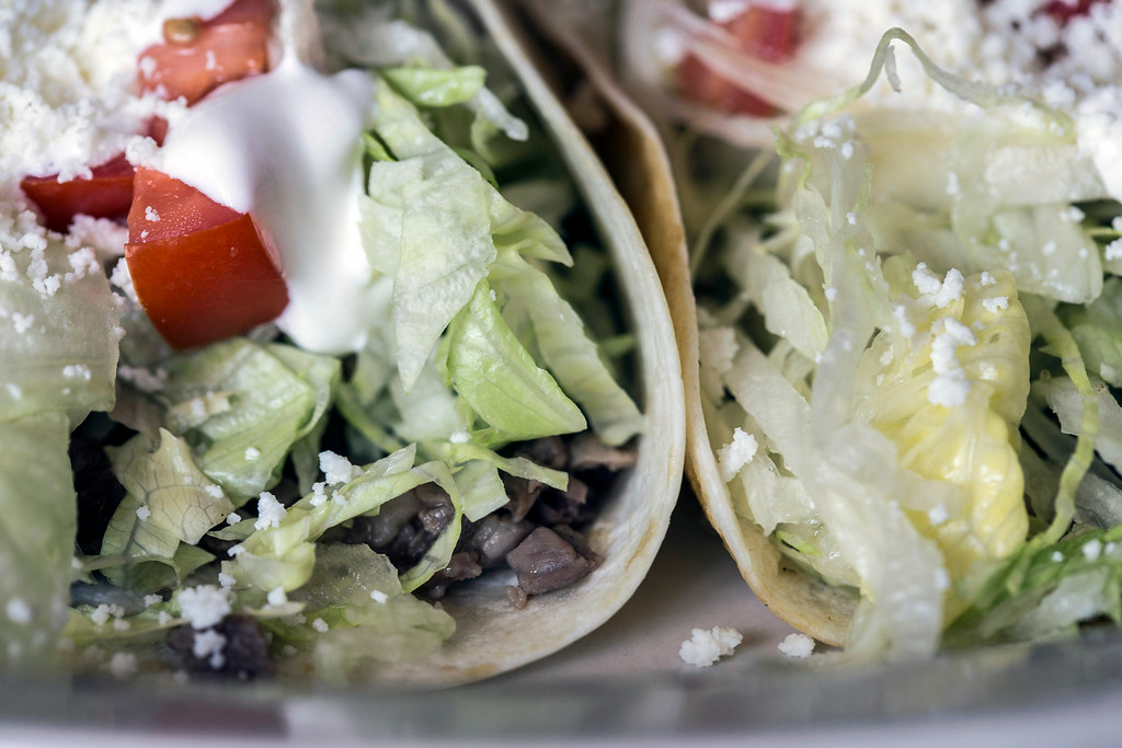 """The """"classic"""" tacos at El Mariachi Restaurante Mexicano are three tacos topped with lettuce, tomatoes, sour cream and fresco cheese."""