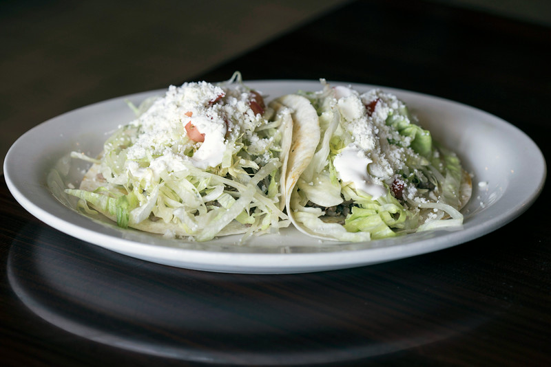 "The ""classic"" tacos at El Mariachi Restaurante Mexicano are three tacos topped with lettuce, tomatoes, sour cream and fresco cheese."