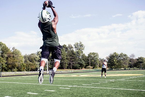 Floyd Central fullback Garry Posey gets a little air during practice throws with quarterback Colton Kimm.
