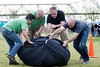 (Left to right) Kentucky Derby Festival members Leslie Brocker, David Nett, Mike Berry, and Jeff English complete the daunting task of pushing 225-lbs through 75-ft of obstacle course during the 2nd Annual Balloon Crew Challenge on the Waterfront Lawn Thursday night.