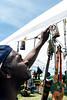 Lonnie Barrett hangs a Bob Marley drink holder on his Goma Trading booth at the Kentucky Reggae Festival. 5/23/15