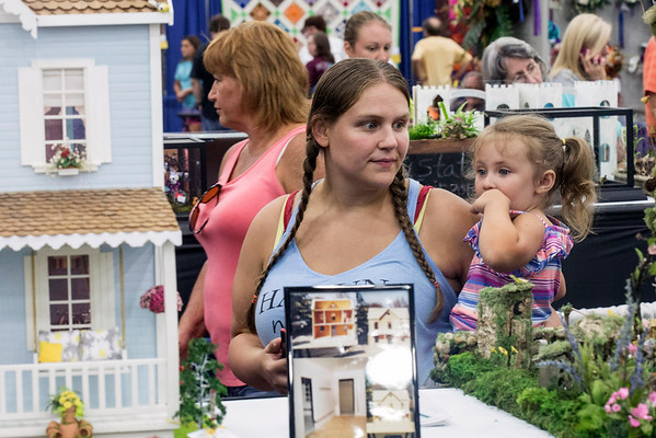 Brittany Grunden and her daughter take in the swirling detail of the dollhouse exhibit at the Kentucky State Fair. 8/24/16