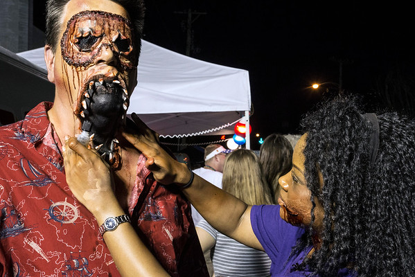 Nikki Miller helps Tinsley Happel with a little impromptu jaw surgery during the annual Zombie Walk on Saturday night. 8/27/16