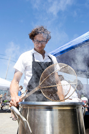 Nate Snyder mans the fryer preparing French fries to be paired with Elmwood stock beef at the Decca booth during FEAST O.F.F. on Saturday. 9/3/16