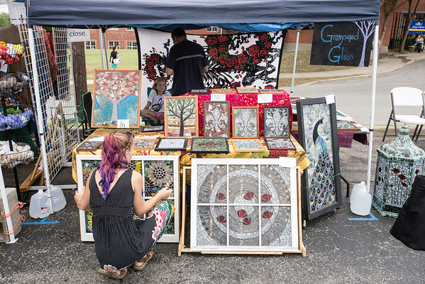 Chanda Froehle adjusts some of her merchandise in the Groovysquid Glass booth at the September Art Fair on Saturday afternoon. 9/10/16