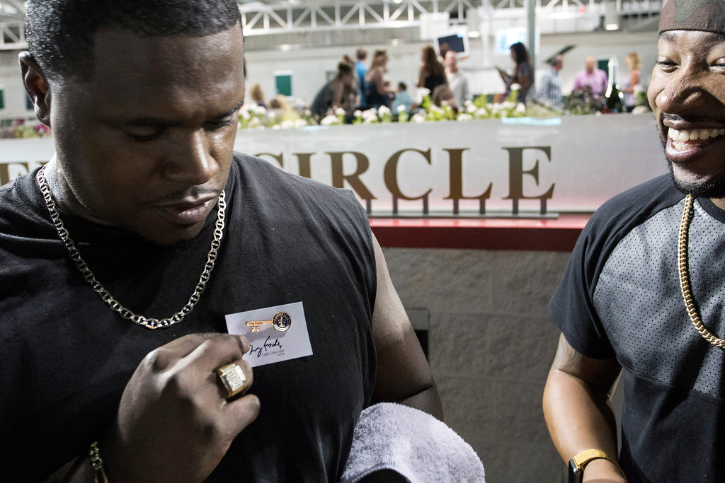 Big Rome Kimbrough of Linkin' Bridge checks out how his newly awarded key to the city pin will look on him during Downs After Dark on Saturday night. 9/24/16