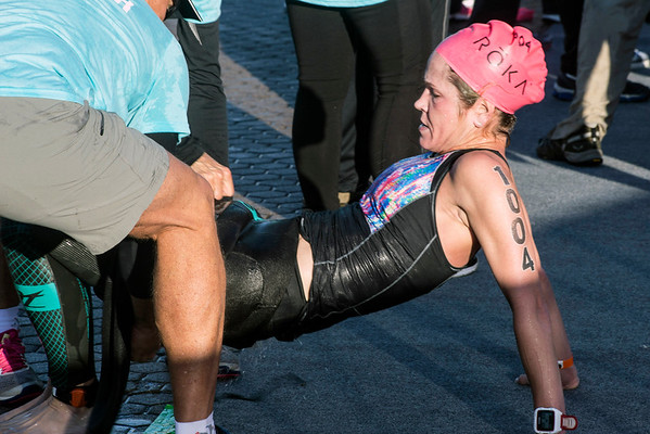 Carrie Reuwer of Chesterfield, MO gets some assistance with her suit after completing the 2.4 mile swim of the Ironman in 00:58:43 on Sunday morning. 10/9/16