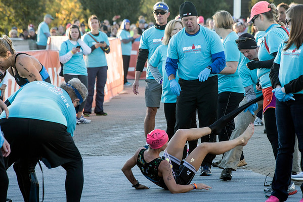 Katherine Wayman of Columbus, OH gets help with removal of her suit after completing the 2.4 mile swim course of the Ironman in 01:01:18 on Sunday morning. 10/9/16