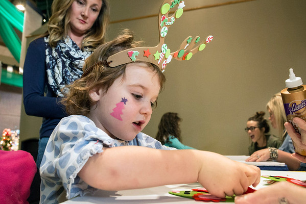 Christy Vensel watches Mollie Bourke create a paper ornament in the children's activities area of the 2016 Festival of Trees & Lights on Friday. 11/11/16