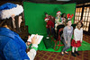Elf Amber Mulhall assists a group of children as they enjoy the Santa's Sleigh Green Screen booth at Christmas at the Galt House. 11/19/16