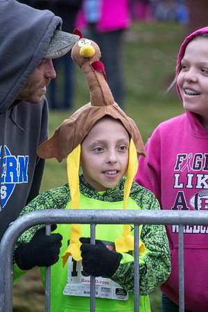 Chase Perryman wears a turkey hat as he stands with Ricky Perryman and Brooklyn Wood to cheer on family in the 46th Annual Turkey Trot. 11/24/16