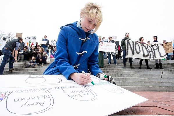 NKU student Celeste Shearer crafts a protest sign before the start of a Standing with Standing Rock rally on the steps of the Kentucky State Capitol Building. 12/4/16