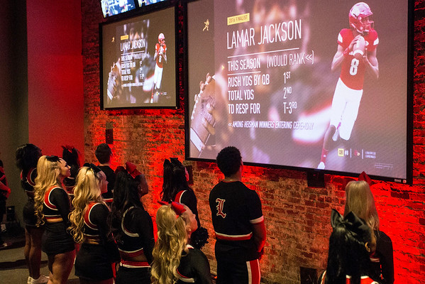 The UofL cheerleaders watch as a season recap video of Lamar Jackson is played during the Heisman broadcast at Sports & Social Club on Saturday night. 12/10/16