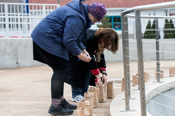 The Rev. Nancy Woodworth-Hill and Patty Ballard light 89 candles around the fountain at the Big Four Station in Jeffersonville on Sunday to honor the victims of 2016's drug overdoses in Clark County. 1/29/17