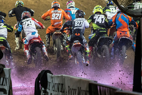 A pack of riders kick dirt as they embark on another fast-paced heat during a line-up of races at the 2017 AMSOIL Arenacross Tour on Saturday. 2/4/17