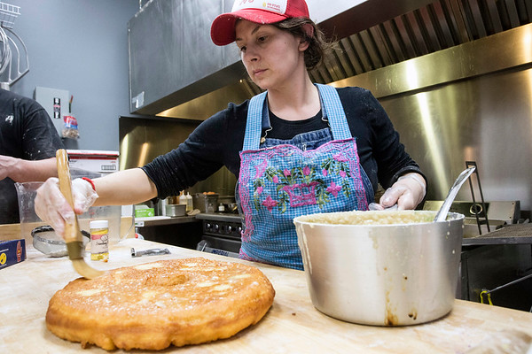 Hi-Five Doughnuts co-owner Leslie Wilson prepares a giant doughnut to be decorated as a king cake for Mardi Gras season. 2/11/17