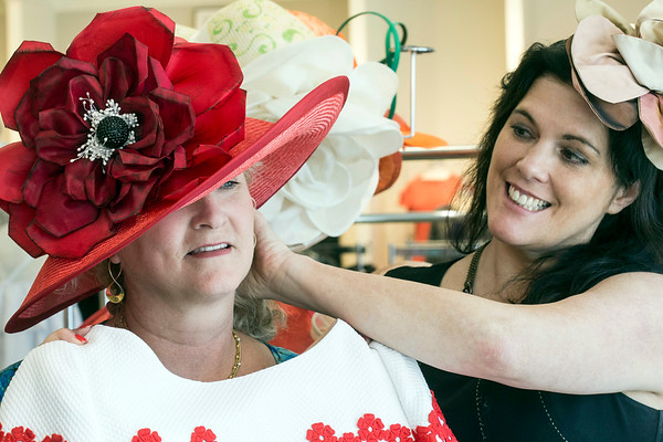 New York City milliner Christine A. Moore makes a few adjustments for customer Beth Scinta during a recent stop at Rhodes for Her. 3/9/17
