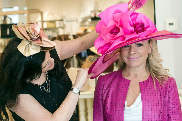 Rhonda Jo Conner tries on one of the colorful creations of milliner Christine Moore available at Rhodes for Her. 3/9/17