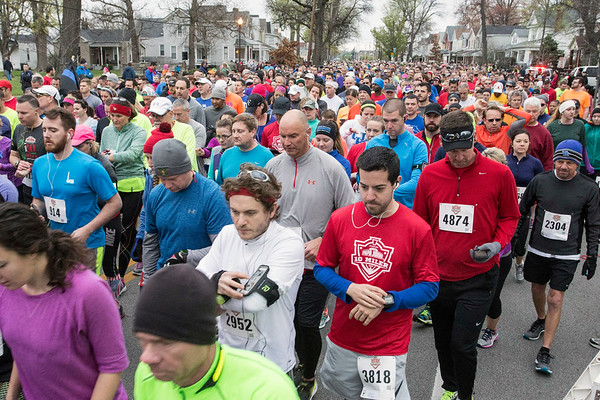 Runners sync their watches as they approach the starting line of the Papa John's 10-Miler. 4/1/17