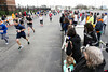 Fans watch from the stadium parking lot as runners in the Papa John's 10-Miler near the finish line. 4/1/17