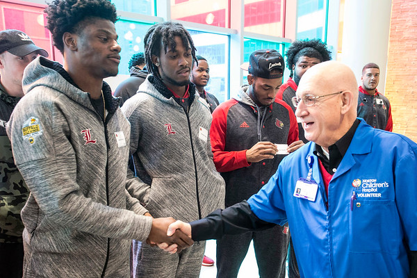 Norton volunteer Gary Byrne greets UofL football players as they arrive at the Children's Hospital on Chestnut for a day of community service. 4/6/17