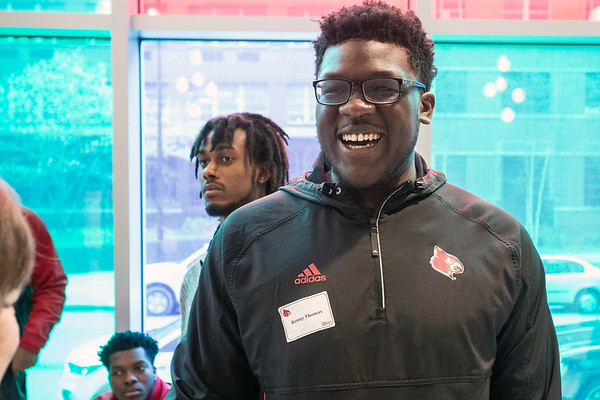 UofL offensive lineman Kenny Thomas shares a lighter moment with staff members at Norton Children's Hospital during a community service visit by the team on Thursday. 4/6/17