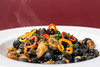 Steam rises from a freshly sauteed plate of Orecchiette at Mercato Italiano. The dish is a colorful mix of shrimp, nduja (spicy) sausage, pickled Italian peppers with squid ink in a shellfish broth. 5/23/17