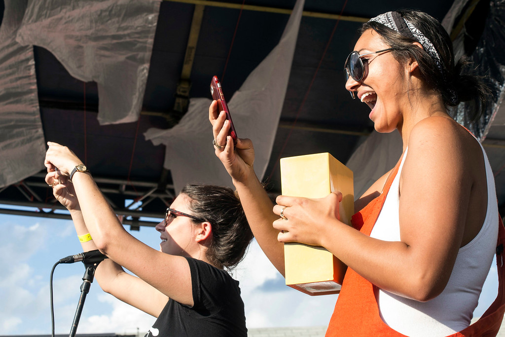 Poorcastle Festival co-founder Shaina Wagner (left) and Victoria Vasquez take a few audience photos during a raffle drawing between music sets on Saturday. 7/8/17