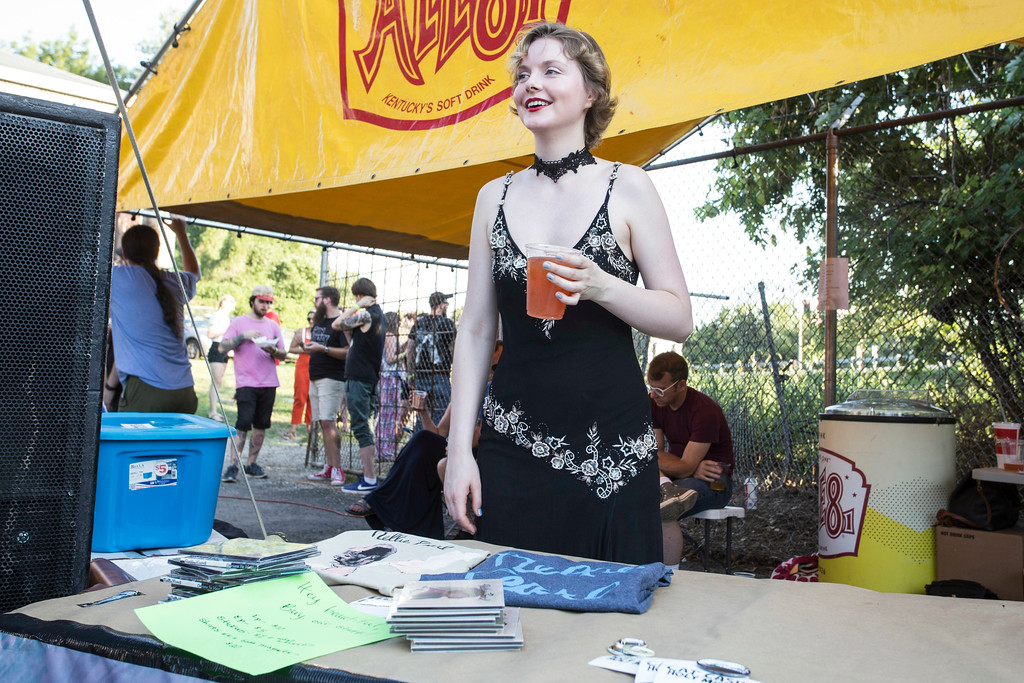 Rachel Lauren Monroe of the band Nellie Pearl takes a shift at the merch booth after her performance during day two of the Poorcastle Festival. 7/8/17