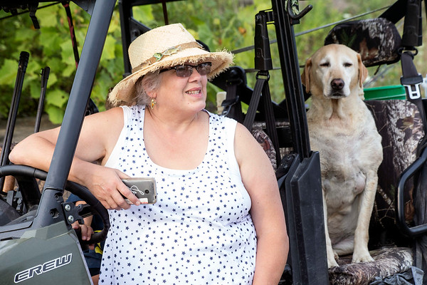 Mystery Lake owner Jeanine Raymond sits with her dog Bayley as members of the UofL football team arrive for a Kentucky Pro Bass Warriors event on Saturday morning. 7/22/17