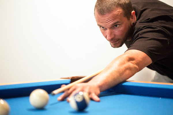 Erik Gunn lines up a shot on the pool table in his PRP home. Gunn enjoys the perks of home ownership for the first time having purchased the house in January. 7/30/17