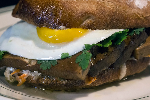 The Tofu Bahn Mi at The Gralehaus is served with pickled daikon, carrot, jalapeno, mayo, cilantro, on a pugliese roll with an optional sunny side up egg for another $1. 8/11/17
