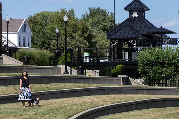 Denise Greer walks her dog Kunu in the grass near the River Stage in Jeffersonville. A lower cost of living and access to the river have been perks of her recent relocation from Louisville. 8/24/17