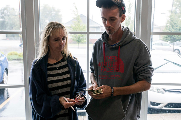 Debbie Alfred takes cash from her son Ryan Young at the PNC on Preston to help the recovering addict pay his bills while fighting off his addictions. 9/1/17
